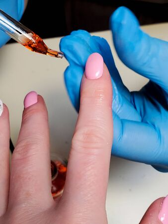 manicurist holds the client's hands, applying nourishing oil to the cuticle.
