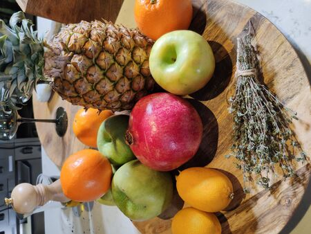 Fresh fruit pineapple pomegranate Apple orange lemon on a wooden Board.