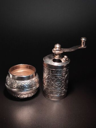 Spice and pepper mill on an isolated dark background.