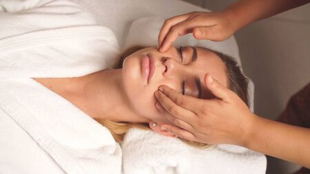 Anti-aging facial massage. A pretty woman in complete relaxation from a facial massage.