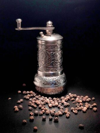 Iron pepper mill and scattered pepper on a black background.