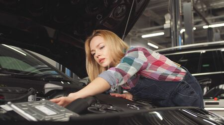 Woman is studying to be a car mechanic, car repair is her favorite occupation.