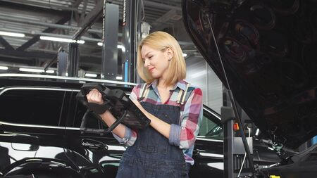 Cute blonde car mechanic engaged in car diagnostics, small business.