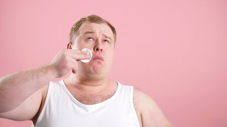 Funny fat man in a t-shirt applying tonic with a cotton pad on his face, on an isolated pink background in the Studio. 版權商用圖片