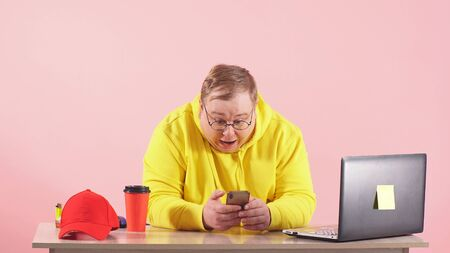 shocked and surprised man in yellow sportswear is sitting at a table watching the news on a pink background on his smartphone. Stok Fotoğraf
