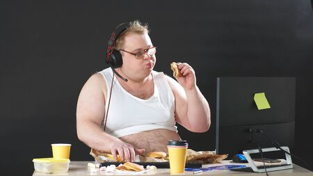 fat man with glasses and headphones sitting at a table eating and playing a PC game at home. Self-isolation, quarantine. Banco de Imagens