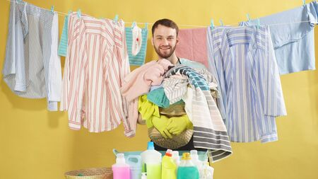 man with a beard holds a Laundry basket and looks at the camera against an isolated background. Clean clothes hang on a clothesline. Banco de Imagens