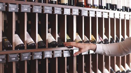 Close-up of a mans hand selecting a bottle of wine from a shelf in a store.