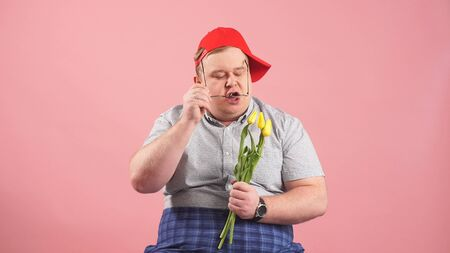 funny man who looks very much like Winnie-the-Pooh with yellow tulips in his hands on an isolated pink background.
