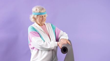 Smiling woman with gray hair is about to practice yoga exercises. isolated background.