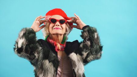 Portrait of a cheerful elderly woman in sunglasses on an isolated background.