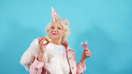 Positive pensioner with a cap on her head poses in the Studio. the concept of birthday.