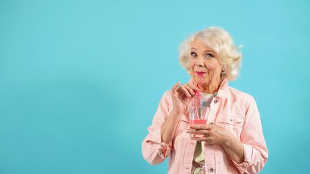 happy pensioner with light hair holds a glass and poses in the Studio on an isolated background.