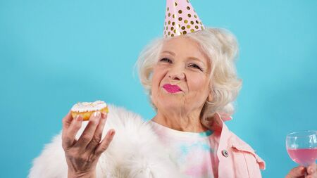Happy pensioner celebrates her birthday, a photo of a woman on an isolated background. Stock Photo