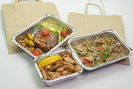 Paper bag meat and steak in their foil containers on an isolated white background. The view from the top, Stock Photo