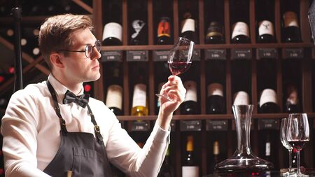 An experienced sommelier looks at the wine in the glass. Wine tasting in a wine boutique, close-up.