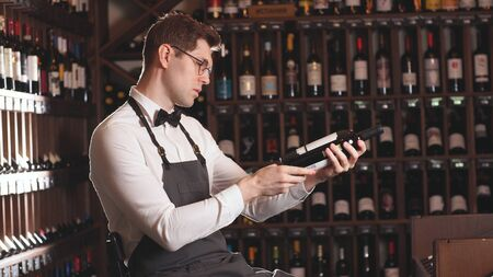male wine seller selects wine for customers in a wine store.