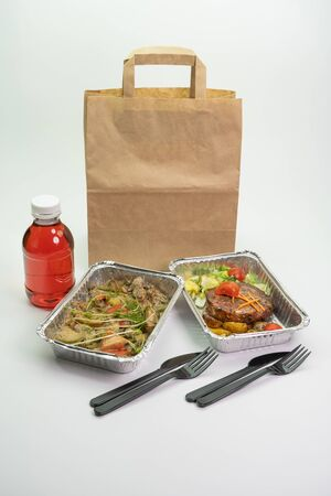 Kraft bag of compote, meat and steak in their foil containers on an isolated white background. The view from the top, Stock Photo