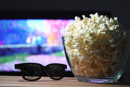 popcorn 3D glasses and TV in the background. Evening movie viewing at home on self-isolation. Stock Photo
