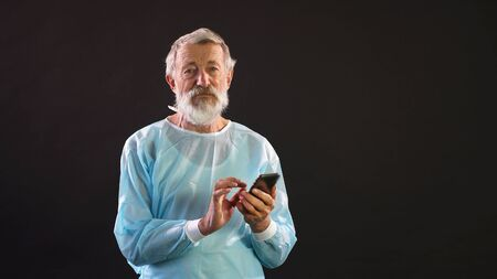 An old doctor, a surgeon uses a smartphone on a dark background. Portrait of an old man in a medical suit.