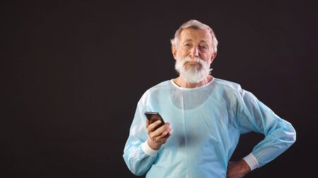 white-haired male doctor, a surgeon in a medical suit uses a smartphone on an isolated dark background and looks at the camera.