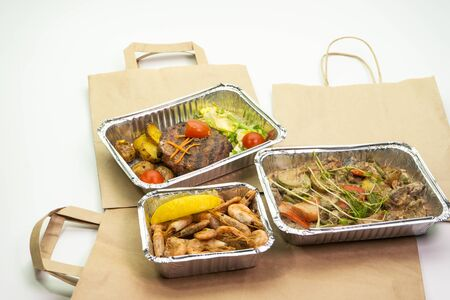 Delicious meals with daily delivery. Fitness food, vegetables, meat and Morse, compote in foil boxes, Cutlery in a paper bag on a white background. Banque d'images