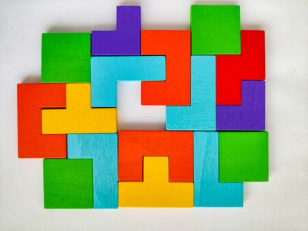 Details of a wooden multi-colored puzzle. Pieces of a color puzzle puzzle on an isolated background.