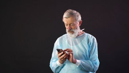 Elderly male doctor in a medical suit with a phone in his hands on an isolated dark background.