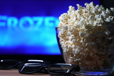 glass bowl of popcorn and 3D glasses in the background a TV is running. In the evening, we watch movies sitting at home on self-isolation due to the covid-19 pandemic. Stock Photo