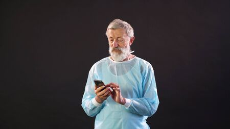 Portrait of a doctor typing on a smartphone. Portrait of an elderly man with gray hair and beard. Dark isolated background.