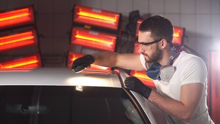 Man in gloves car polishing specialist checks the result of polishing with a flashlight.