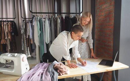 female designer shows her hand-made clothing sketches to a beautiful client. The concept of fashion design.