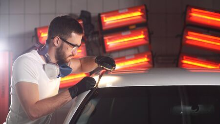 man with a beard and gloves with a flashlight is busy checking the quality of polishing the car body.