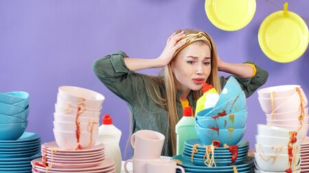 young woman in a panic, terrified of the number of unwashed dirty plates and cups. Stock Photo
