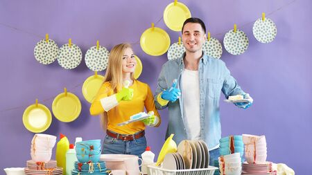 Positive young woman and a black-haired man give a thumbs up while holding clean plates. clean plates hang on clothespins in the background.