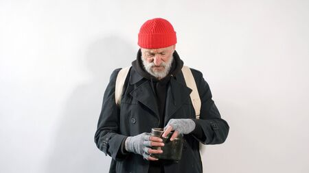 homeless man, a pensioner, an old man with a gray beard in a coat and a red hat on an isolated white background.