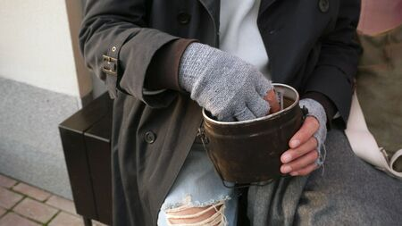 Male hands of a homeless old man holding a bowl, a glass for donations. Banco de Imagens