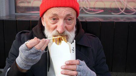 Tired wrinkled old man, homeless, elderly man eating wok noodles on the street. close-up