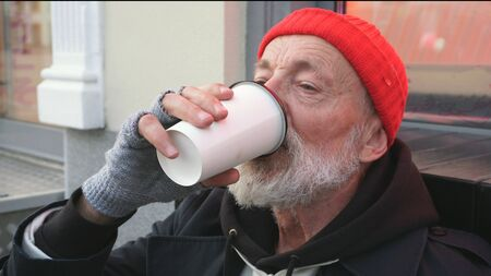Bearded old man, homeless man drinking a hot drink to keep warm. A tired homeless man drinks tea sitting on a cardboard on the street.