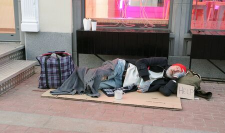 Elderly man, an old man, a beggar, a homeless man sleeping on cardboard directly on the street. A homeless old man with a help sign sleeps on cardboard on the street holding an empty bottle.