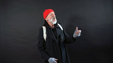 Old man with a gray beard, a pensioner, an elderly man dressed in a coat and a red hat reads poems on an isolated dark background.