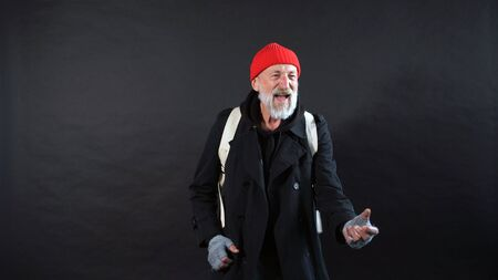 homeless man, a pensioner, an old man with a gray beard in a coat and a red hat on an isolated dark background. Banco de Imagens