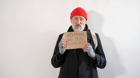 Male aged tramp, homeless old man with a gray beard in a coat and a red hat with a sign request for work in his hands, isolated white background.