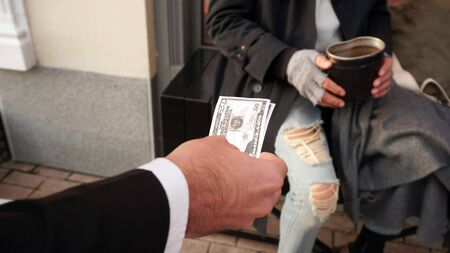 People reach out with money, dollars to a homeless person, a beggar to help, to give money for a donation.