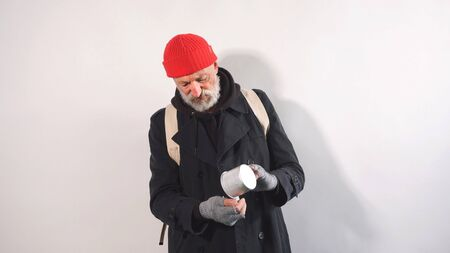 aged Man, beggar, homeless old man with a gray beard in a coat and a red hat pours coins out of a glass on an isolated background.