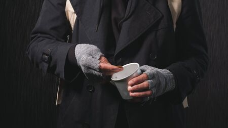 Close-up of the hands of a homeless old man, a homeless man counting coins to eat and drink.