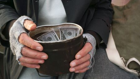 Close-up of mens hands holding financial aid, dollars. Homeless, old man holding dollars in his hand.