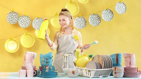 Charming young woman on an isolated background and a pile of dirty dishes.