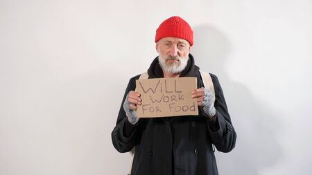 Male aged tramp, homeless old man with a gray beard in a coat and red hat with a sign for help in his hands, isolated white background.