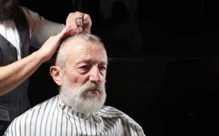 gray-Haired pensioner sits in a Barber shop, barbershop on a haircut. A Barber cuts the hair of an elderly old man, a man aged.